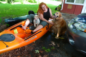 Woman on kayak with two dogs